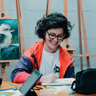 Aluna do Ateliê de pintura da Escola Casa, sorrindo ao fazer seu esboço. Sala de pintura na Escola Casa em Blumenau