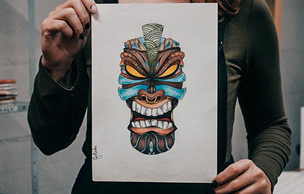 Aluna segura seu desenho com estilo totem de referência africana colorido e criado nas aulas do curso de Desenho e Ilustracao
