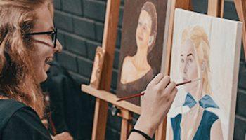 Aluna do ateliê de pintura da Escola Casa, sorrindo e pintando em óleo sobre tela.